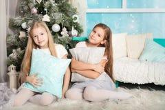 Dos muchachas en decoraciones de una Navidad Imagen de archivo libre de regalías