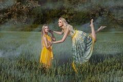 Dos muchachas en el campo Una muchacha eleva y mantiene flotando Foto de archivo libre de regalías