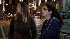 Dos muchachas en el circo en la noche - Londres de Piccadilly que hacen turismo por noche almacen de metraje de vídeo