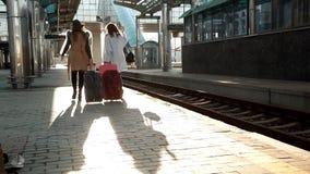 Dos muchachas en el ferrocarril con sus maletas hacia fuera en la plataforma que espera el tren almacen de metraje de vídeo