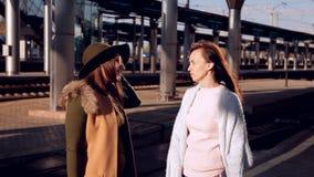 Dos muchachas en el ferrocarril con sus maletas hacia fuera en la plataforma que espera el tren almacen de video