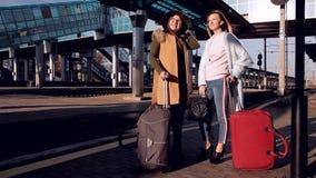Dos muchachas en el ferrocarril con sus maletas hacia fuera en la plataforma que espera el tren metrajes