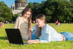 Dos muchachas en el parque con un ordenador portátil Fotos de archivo libres de regalías