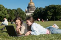 Dos muchachas en el parque con un ordenador portátil Imágenes de archivo libres de regalías