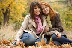 Dos muchachas en el parque del otoño. Imagenes de archivo