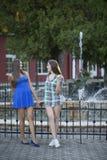 Dos muchachas en el parque delante de las fuentes Fotografía de archivo