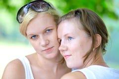 Dos muchachas en el parque uno del verano miran en cámara Foto de archivo libre de regalías