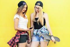 Dos muchachas en el patio que miran las noticias en el smartphone en redes sociales imagen de archivo libre de regalías