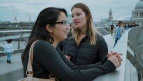 Dos muchachas en el puente del milenio en Londres - ciudad que hacen turismo almacen de metraje de vídeo