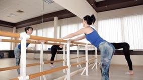 Dos muchachas en el tren del estudio del ballet en el banco y el espejo Flexibilidad, ejercicio, danza almacen de video