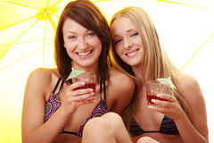 Dos muchachas en ensaladas de fruta de la bebida del bikiní Imagen de archivo libre de regalías