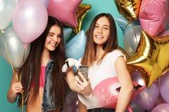 Dos muchachas en equipo elegante del verano, los vidrios de papel y el bal del aire Imagen de archivo