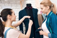 Dos muchachas en la fábrica de la ropa desining el nuevo hombre se adaptan a la chaqueta imagenes de archivo