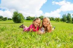 Dos muchachas en la hierba con la mariposa Imagen de archivo libre de regalías