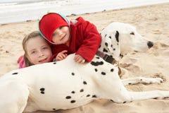 Dos muchachas en la playa con el perro de animal doméstico Fotos de archivo libres de regalías