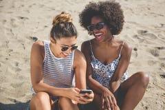 Dos muchachas en la playa usando la risa móvil Foto de archivo