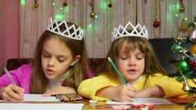 Dos muchachas en las batas que se sientan en la tabla y puestas su cabeza en sus manos que escribe la letra a Santa Claus metrajes