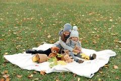 Dos muchachas en los casquillos grises arreglan una comida campestre en parque del otoño por la tarde Imágenes de archivo libres de regalías