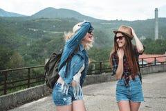 Dos muchachas en los sombreros que viajan a través de ander de las ruinas llueven Fotos de archivo libres de regalías