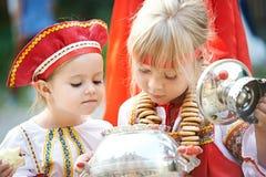 Dos muchachas en los trajes nacionales rusos con el samovar Fotos de archivo libres de regalías