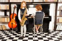 Dos muchachas en los vestidos de la escuela que juegan en los instrumentos Imagenes de archivo