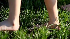 Dos muchachas en los vestidos de lino blancos caminan a lo largo de un prado verde en un día de verano Carrocería parts almacen de video
