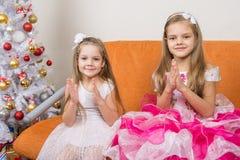 Dos muchachas en los vestidos hermosos que conjeturan los regalos por Año Nuevo Imagen de archivo