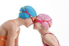 Dos muchachas en mirada de los trajes de natación en uno a Foto de archivo