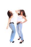 Dos muchachas en pantalones vaqueros y la camiseta blanca Foto de archivo