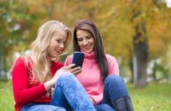 Dos muchachas en parque con un teléfono móvil en otoño Foto de archivo libre de regalías
