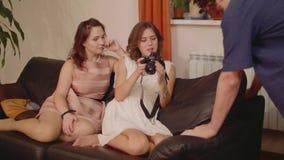 Dos muchachas en ropa sofisticada se sientan en muchacha del sofá uno hacen imágenes almacen de video