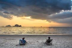 Dos muchachas en sillas de playa que admiran la puesta del sol en el mar imagen de archivo