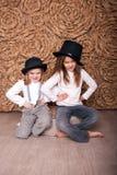 Dos muchachas en sombreros negros imagenes de archivo