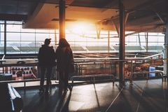 Dos muchachas en terminal de aeropuerto cerca de la ventana fotografía de archivo libre de regalías