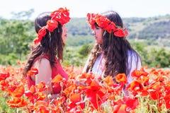 Dos muchachas en un campo de las flores de la amapola Fotografía de archivo