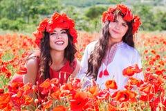 Dos muchachas en un campo de las flores de la amapola Foto de archivo
