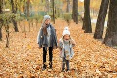 Dos muchachas en un gris capsulan la situación en parque del otoño por la tarde Fotos de archivo