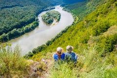 Dos muchachas en un top de la montaña sobre el barranco del río fotografía de archivo libre de regalías