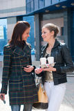 Dos muchachas en una calle con café Fotos de archivo libres de regalías