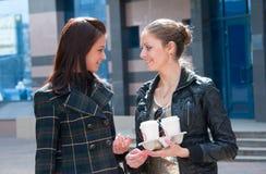 Dos muchachas en una calle con café Imagen de archivo libre de regalías