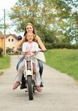 Dos muchachas en una moto Foto de archivo