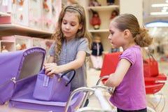 Dos muchachas en una tienda de juguete con las muñecas compraron un cochecillo y un bolso Fotografía de archivo