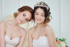 Dos muchachas en vestidos de boda Muchachas delicadas hermosas en el salón nupcial Foto de archivo