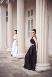 Dos muchachas en vestidos largos blancos y negros Imagenes de archivo