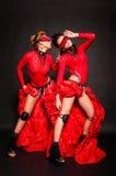 Dos muchachas en vestidos rojos Fotos de archivo