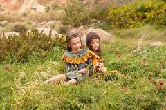 Dos muchachas en vintage retro visten las flores de la cosecha en un campo del prado Imágenes de archivo libres de regalías