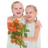Dos muchachas encantadoras con los ramos de rosas. Fotos de archivo libres de regalías