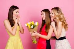 Dos muchachas encantadoras que dan el ramo de tulipanes coloridos a su franco Imagenes de archivo
