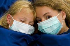 Dos muchachas enfermas en cama Imagenes de archivo