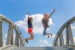 Dos muchachas entusiastas que saltan en el puente Foto de archivo libre de regalías